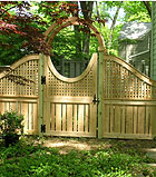 semi private wood fence with scalloped square lattice with an arbor and scalloped gate