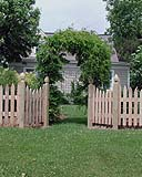 spaced scalloped white cedar wooden picket fence with arbor by elyria fence